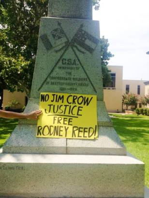 "A supporter holds a sign saying ""No Jim Crow Justice"" in front of a Confederate monument at the Bastrop Co. Courthouse"