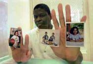 Rodney holds pictures of his children inside the visitation booth at Texas Death Row