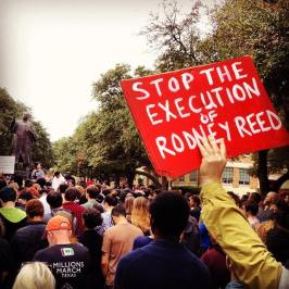 "Supporter holds a sign reading ""Stop the Execution of Rodney Reed"" in a crowd gathered around the Martin Luther King, Jr statue at the University of Texas at Austin. Picture by Hooman Hedayati"