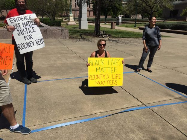 Outside the Court of Criminal Appeals, a supporter kneels inside a 6' x 10' area representing the size of cells on Texas death row